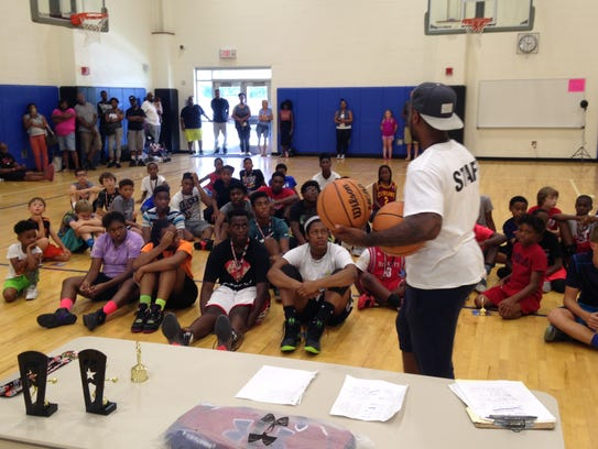 Andre Collins hands out awards to the campers on the