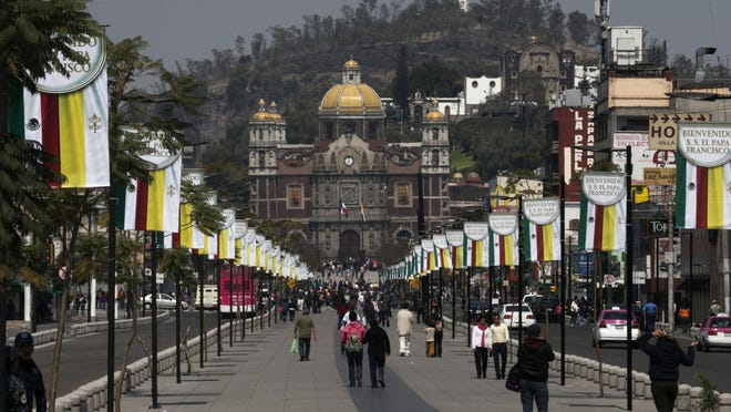 Signs welcoming Pope Francis decorate the walkway leading to the Basilica of Guadalupe on Thursday in Mexico City. The pontiff arrives in Mexico on Friday.