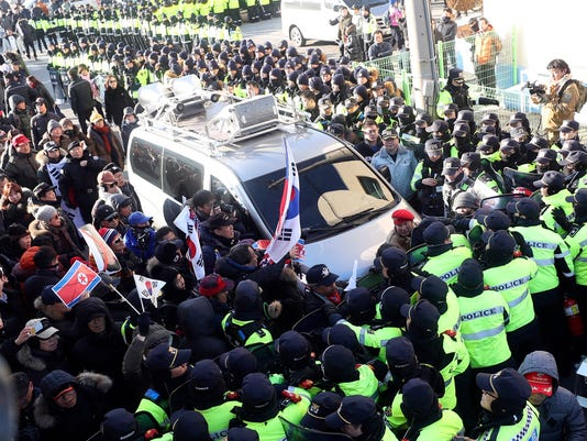 Members of conservative civic groups scuffle with the police officers during a protest against North Korea as North Korea's Mangyongbong-92 ferry, carrying North Korea's members of art troupe approaching to Mukho Port in Donghae, South Korea, Tuesday, Feb. 6, 2018. The art troupe, led by Hyon Song Wol, also the leader of the famous Moranbong girl band hand-picked by North Korean leader Kim Jong Un, will perform in Gangneung and Seoul on Feb. 8 and Feb. 11, respectively, before returning home. (Choo Sang-chul/Newisvia AP)