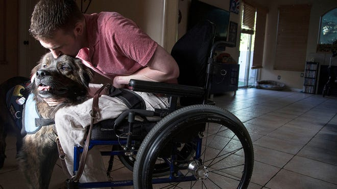 Cory Remsburg (hugging his dog, Leo, at his rental home in Gilbert) was wounded in Afghanistan in 2009 while serving as an Army Ranger and was spotlighted by President Obama in his 2014 State of the Union address. Today, Remsburg will move into a retrofitted home that will help him reclaim independence.