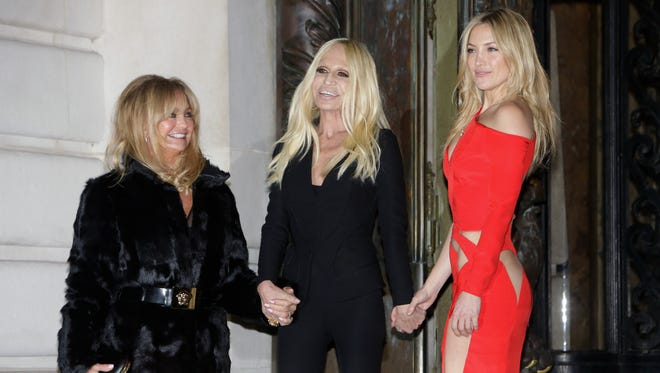 From left, Goldie Hawn, Donatella Versace and Kate Hudson pose as they arrive for the show of the Atelier Versace Spring-Summer 2015 Haute Couture fashion collection presented in Paris, France, Sunday, Jan. 25, 2015.