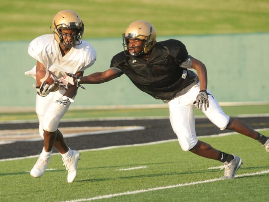 Abilene High receiver Jashari Houston, left, hauls in a catch while being defended by Nate Jones. Houston scored on the play during the Eagles' annual Black and Gold spring football game Tuesday, May 22, 2018 at Shotwell Stadium.