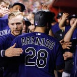Colorado Rockies' Nolan Arenado (28) gets a hug from Trevor Story, left, after hitting a home run against the Arizona Diamondbacks during the fifth inning of a baseball game Friday, April 29, 2016, in Phoenix. (AP Photo/Ross D. Franklin)