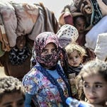 Syrian Kurds carry their belongings as they cross the border between Syria and Turkey at the southeastern town of Suruc in Sanliurfa province on Tuesday, Sept. 23, 2014. Syrians are fleeing attacks by the Islamic State. A U.S.-led international coalition conducted air strikes against the militant group late Monday.