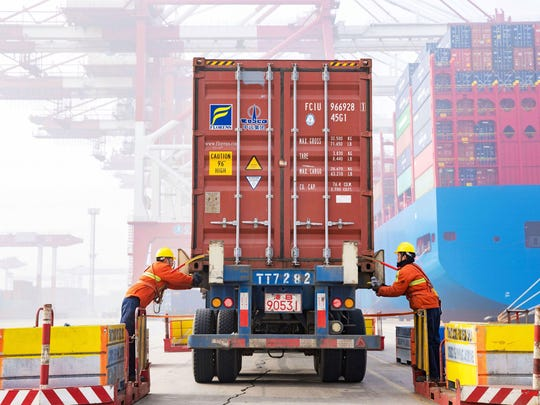 Workers prepare a container at the port in Qingdao, China's eastern Shandong province, on Jan. 14, 2019.