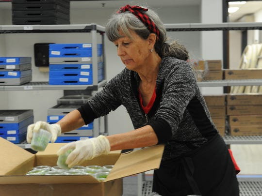 Louise Smith, a child nutritional worker, puts edamame into boxes for the summer meal program in the Ventura Unified School District. Workers prepare the meals each morning beginning at 5 a.m. and they are then delivered to school sites where they are served.