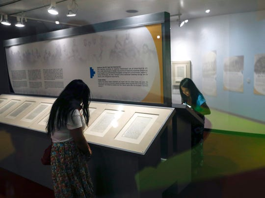Visitors inspect the pages of the treaty of 1868 Friday at the Navajo Nation Museum in Window Rock, Arizona.