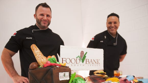 Manny Agigian  (left) and Al DiBartolo, both of DiBartolo's Bakery in Collingswood, pose for a portrait in front of a cake they created for the 2014 fall event.