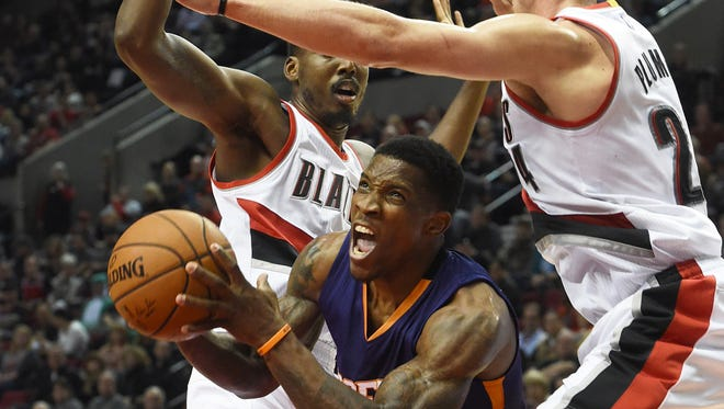 Phoenix Suns guard Eric Bledsoe, center, drives to the basket on Portland Trail Blazers forward Al-Farouq Aminu, left, and forward Mason Plumlee, right, during the first quarter of an NBA basketball game in Portland, Ore., Saturday, Oct. 31, 2015.