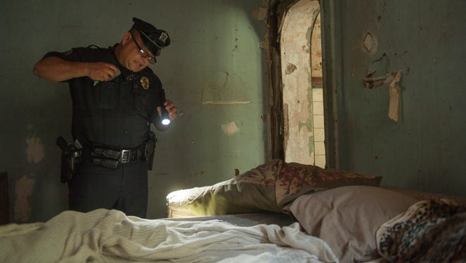 Camden County Police Officer Hector Ramirez clears an abandoned house in Camden. Camden County Police Chief Scott Thomson has indicated his officers are pushing the violence out of the streets and that most slaying are happening indoors or in cars.