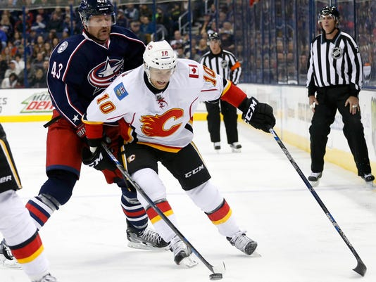 Columbus Blue Jackets' Scott Hartnell, left, knocks the puck away from Calgary Flames' Kris Versteeg during the first period of an NHL hockey game Wednesday, Nov. 23, 2016, in Columbus, Ohio. (AP Photo/Jay LaPrete)