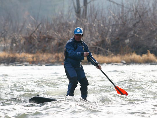 Steve Bush rides a stationary wave on the Chenango River with his stand up paddle board in Chenango Forks on Monday, December 4, 2017.