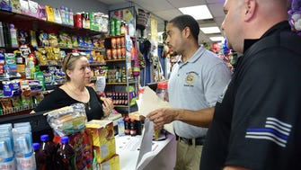 Detective Miguel Sanchez from the Englewood Police, center, and Detective Dennis Conway of the Bergen County Prosecutor's Office speak with Aura Zapata as they walk around Palisades Ave in Englewood handing out fliers concerning the assailant that attacked a 83-year-old female on July 28.