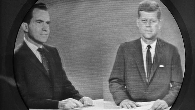 Vice President Richard M. Nixon, left, listens as Senator John F. Kennedy talks during their televised presidential race debate. This photo was made from a television screen in New York, Oct. 21, 1960.