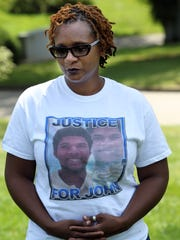Tressa Sherrod,  whose son,  John Crawford III,  22,  was shot and killed by a Beavercreek police officer while holding an air rifle/pellet gun he picked up from a store shelf  in a Beavercreek Wal-Mart store wears a shirt bearing her son's image.  She is in Spring Grove Cemetery where he is buried.