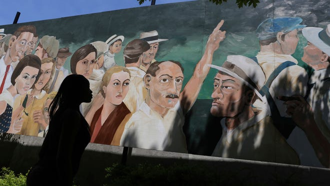 """People gather by the controversial mural painted by artist Dave Powers in Elgin, Ill., on Thursday, May 19, 2016. The Elgin Cultural Arts Commission rejected artist David Powers' request Monday, May 14, 2018, for the return of his piece, """"American Nocturne."""" The city put the mural into storage after learning in 2016 that the painting was based on a crowd photographed during a 1930 lynching in Marion, Ind."""