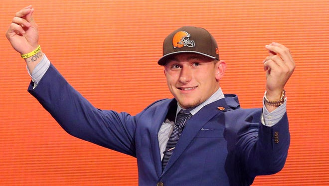 Johnny Manziel (Texas A&M) gestures as he walks across the stage after being selected as the number twenty-two overall pick in the first round of the 2014 NFL Draft to the Cleveland Browns at Radio City Music Hall.