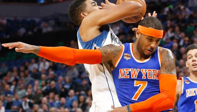Timberwolves' Karl-Anthony Towns, left, is fouled by Knicks' Carmelo Anthony as he attempts a shot during the first quarter Wednesday in Minneapolis. (AP Photo/Jim Mone)