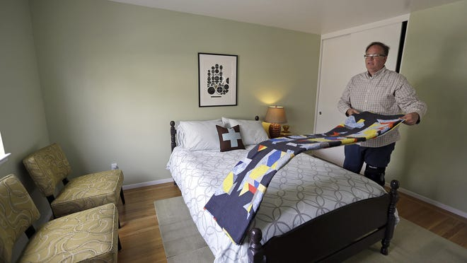 Bruce Bennett folds a blanket in a room that he makes available to rent in his home in San Francisco. Airbnb says the city's new regulation challenges the heart of what makes the internet the flourishing, free-wheeling frontier it is: that internet platforms cannot be sued or punished for the content posted by third-party hosts.