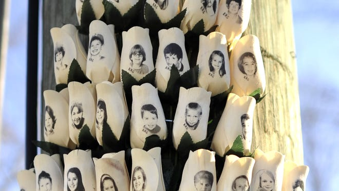 This file photo taken on Jan. 3, 2013 shows roses with the faces of Sandy Hook Elementary school victims in Newtown, Conn.