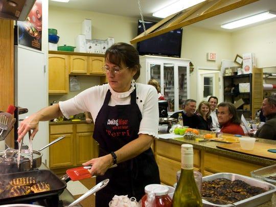 Terri Geiser grills duck breasts during a 2011 Glass Bazaar cooking class.