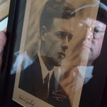 David Mars is reflected in an autographed photo of Charles Lindbergh, one of the many aviation history artifacts he has collected over the years.
