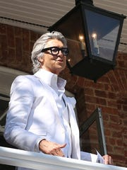 """After the costume parade down to the station and back, Tommy Tune led the crowd in the singing of the movie's title song, """"Hello, Dolly!"""" from the brick building that served as Vandergelder's Hay & Feed Store in the movie."""