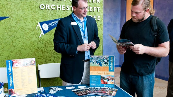 Brett Tyer talks to George Wolf (left) of Westminster College about the school's new program in Mesa in 2012.