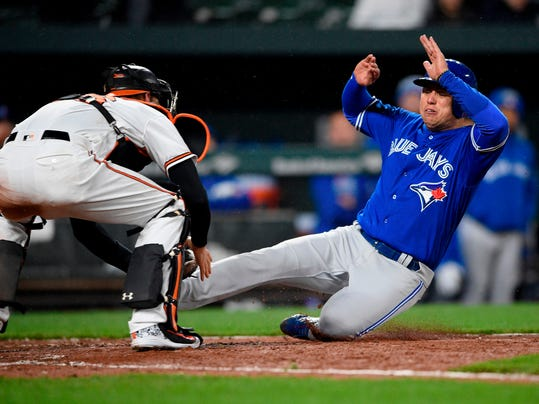 Toronto Blue Jays' Aledmys Diaz, right, is out at the plate against Baltimore Orioles catcher Caleb Joseph, left, during the eighth inning of a baseball game, Monday, April 9, 2018, in Baltimore. (AP Photo/Nick Wass)