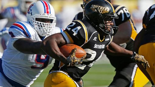 Southern Mississippi running back George Payne (24) runs past Louisiana Tech defensive lineman Vernon Butler (9) for a short gain in the first half of an NCAA college football game in Hattiesburg, Miss., Saturday, Oct. 25, 2014. (AP Photo/Rogelio V. Solis)