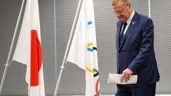 John Coates, chairman of the IOC Coordination Commission for the 2020 Tokyo Olympics and Paralympics walks near a Japanese and the Olympics flags after attending the IOC and Tokyo 2020 joint press conference in Tokyo Thursday, July 12, 2018. (AP Photo/Eugene Hoshiko)