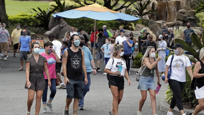 Guests wearing masks stroll through SeaWorld as it reopened with new safety measures in place on Thursday in Orlando. The park had been closed since mid-March to stop the spread of the new coronavirus.