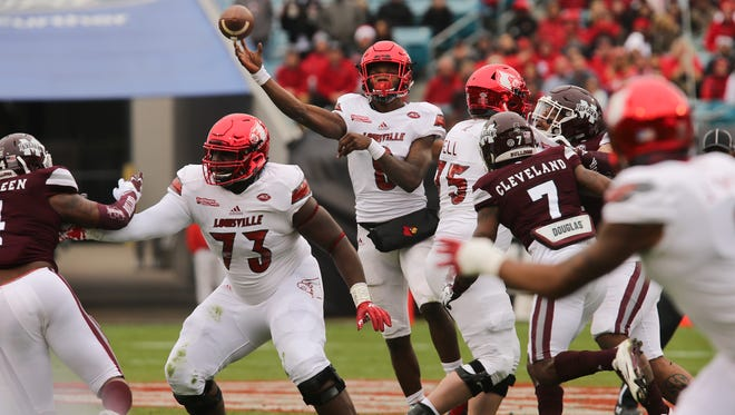 U of L's Lamar Jackson (8) gets some protection as he completes a pass against Mississippi State during the TaxSlayer Bowl in Jacksonville. Dec. 30, 2017