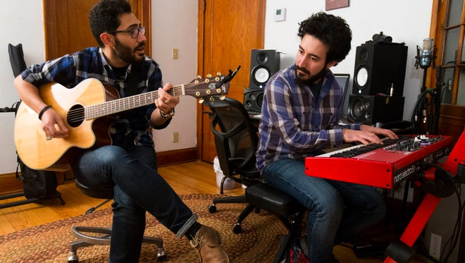 Michal Chabo (left) and his brother, John, play music at the apartment they share in Milwaukee. The brothers fled the besieged city of Aleppo in their native Syria four years ago and moved to Milwaukee two years ago. They were only just granted asylum this summer. Their father was a Christian minister in Syria.