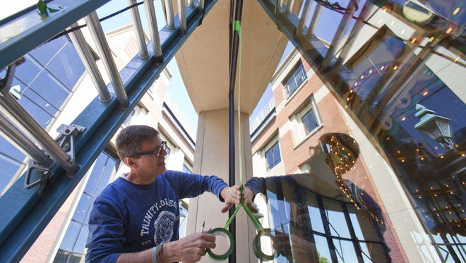 """Patrick Schmidt works on his ArtPrize entry """"How I Make a Mark: Responding to a Carousel"""" at the Grand Rapids Public Museum on Wednesday, Sept. 14, 2016. The tape installation will be on the outside of the museum's carousel. Schmidt is from Pittsburgh."""