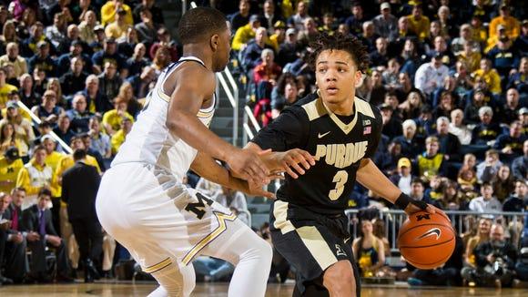 Michigan guard Xavier Simpson, left, defends Purdue