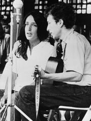 Joan Baez and Bob Dylan perform in 1963 at the Newport Jazz Festival in Newport, R.I. Two years later, on the night of July 25, 1965, Dylan strode onto a stage at the Newport Folk Festival, plugged in an electric guitar and gave the music world a shock.