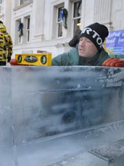Gary Glenn, of DiMartino Ice Co., sets blocks of ice in preparation for carving at IceFest 2012.
