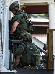 Members of the Lebanon County Emergency Services Unit stand on the porch of 910 Walnut St. where a domestic dispute occurred in which a woman was reportedly threatened by a man with a handgun early Saturday morning led to a police standoff that forced the 900 block of Walnut Street in Lebanon to be shut down for several hours on Saturday, June 24, 2017