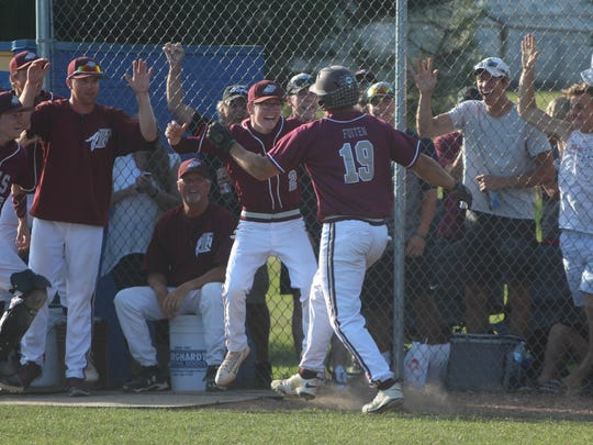 Menomonee Falls players and fans are all smiles as they greet Dayne Fuiten (19) after he hit a go-ahead double and scored a run in Monday's sectional final against Germantown.