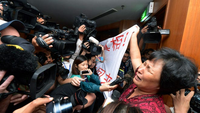 "A Chinese relative of passengers aboard a missing Malaysia Airlines plane cries as she holds a banner in front of journalists reading 'We are against the Malaysian government for hiding the truth and delaying the rescue. Release our families unconditionally!""  at a hotel in Sepang, Malaysia. Malaysian authorities examined new radar data from Thailand that could potentially give clues on how to retrace the course of the Malaysia Airlines plane that vanished early March 8 with 239 people aboard en route from Kuala Lumpur to Beijing. Twenty-six countries are looking for the aircraft as relatives anxiously await news."