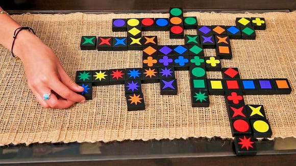 Create sequences of color or shape on a Scrabble-like board.