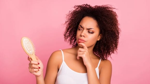 Woman with cury hair looking at brush