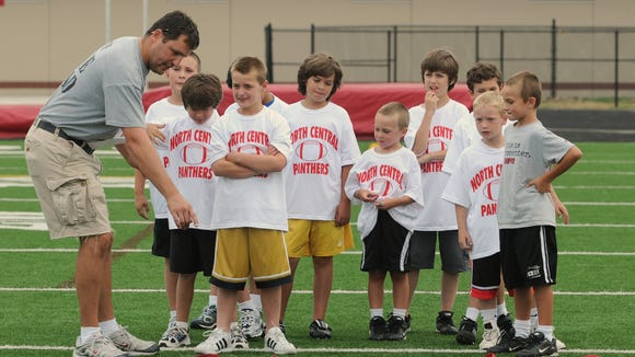 North Central High School football quarterback coach Kevin Kreinhagen explains the ladder drill to players at a football camp for grades 2-5 in 2009.  directed by  North Central High School head football coach Keith Shelton at North Central in 2009.