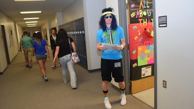 """Pineville High School biology teacher Patrick Kelly dressed the part of a 1980s rocker to greet parents on Tuesday. Pineville High School held a parents' night with a """"Back to the Future""""/1980s theme. The purpose of the night was to welcome parents and show them how to support their children."""