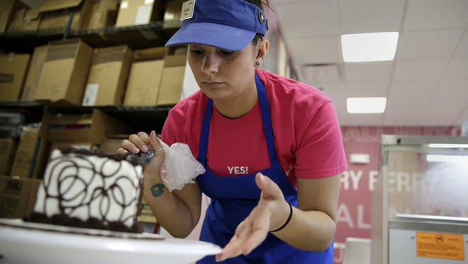 Jasmine Draxler, Baskin-Robbins store manager, finishes decorating an Oreo cake in preparation for the store's opening Monday.