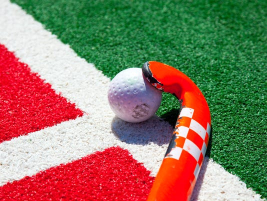 Red and white hockey stick with white ball on the ground