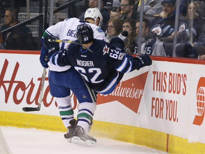 March 26: Jets defenseman Nelson Nogier (62) is hit