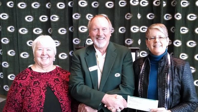 Terry Fulwiler, chairman of Green Bay Packers Foundation, middle, gives a check to the founders of Shirley's House of Hope, Sue Poole, left and Julie Cravillion, right, at Lambeau Field Atrium on Tuesday, Dec. 8, 2015.