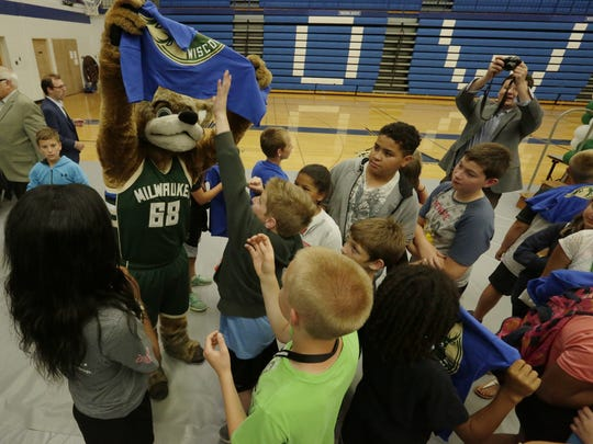 Bango gets in on the action Thursday as he hands out T-shirts to Boys and Girls Club members at the Wisconsin Herd logo unveiling in Oshkosh.